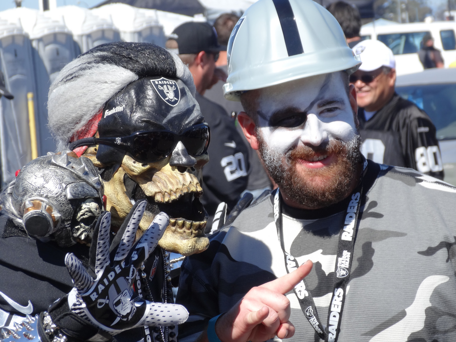 Oakland Raiders fans in costume at tailgate lot